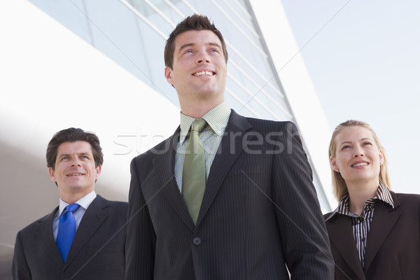 Three businesspeople standing outdoors by building smiling Stock photo © monkey_business