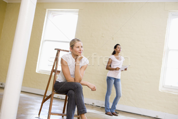 Two women with ladder in empty space holding paper Stock photo © monkey_business