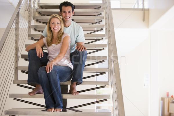 Pár ül lépcsőház mosolyog férfi nők Stock fotó © monkey_business