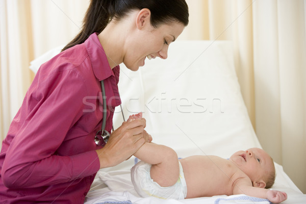 Doctor giving checkup to baby in exam room smiling Stock photo © monkey_business