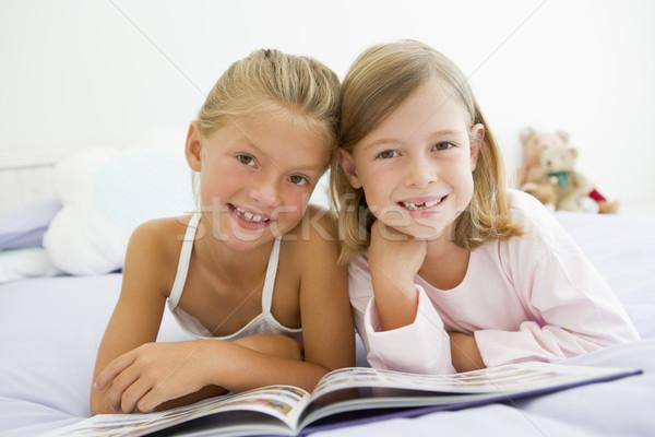 Due giovani ragazze pigiama lettura libro Foto d'archivio © monkey_business