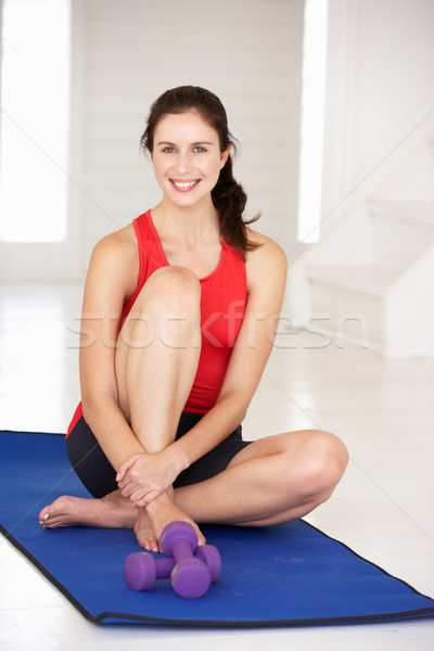 Stock photo: Woman sitting on exercise mat