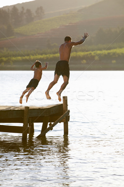 Young man with child jumping to water Stock photo © monkey_business
