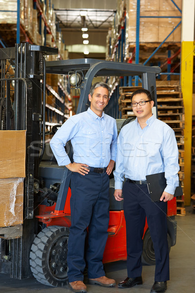 Portrait Of Businessmen With Fork Lift Truck In Warehouse Stock photo © monkey_business