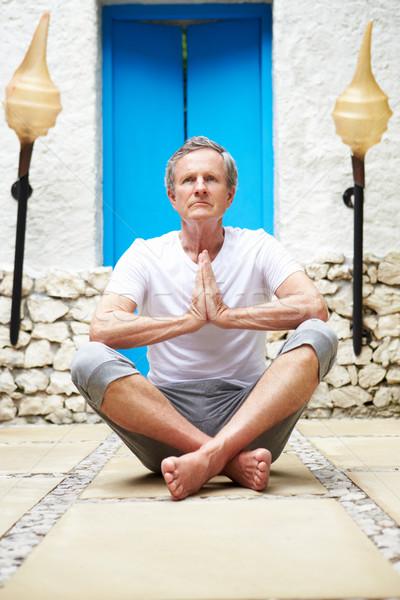 Senior Man Meditating Outdoors At Health Spa Stock photo © monkey_business