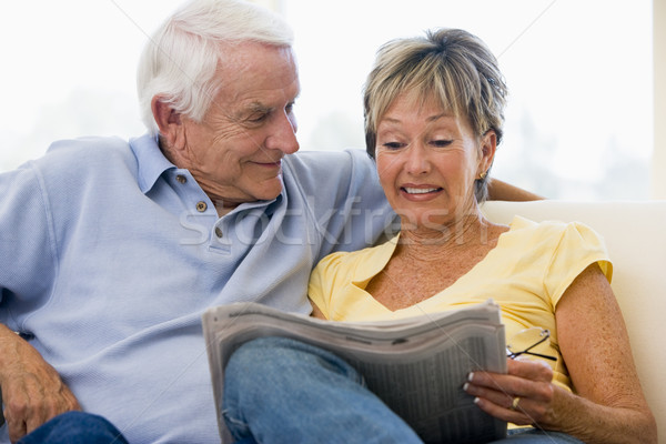 Stock photo: Couple in living room reading newspaper smiling