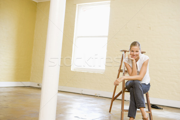 Woman sitting on ladder in empty space smiling Stock photo © monkey_business