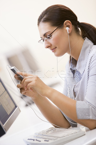 Woman in computer room listening to MP3 Player Stock photo © monkey_business