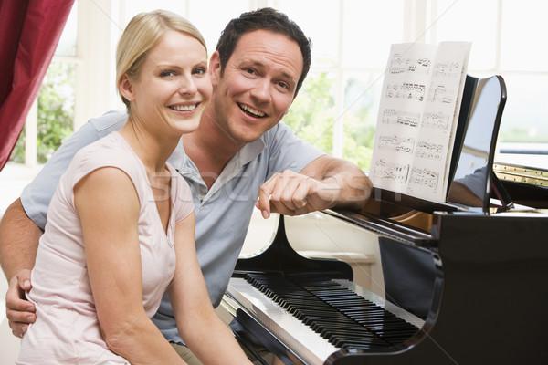 Couple sitting at piano smiling Stock photo © monkey_business