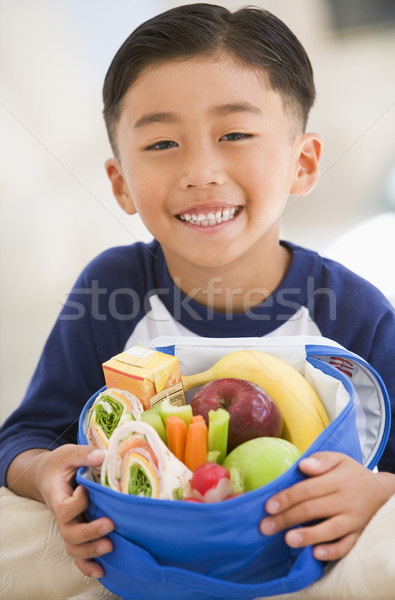 Young boy indoors with packed lunch smiling Stock photo © monkey_business