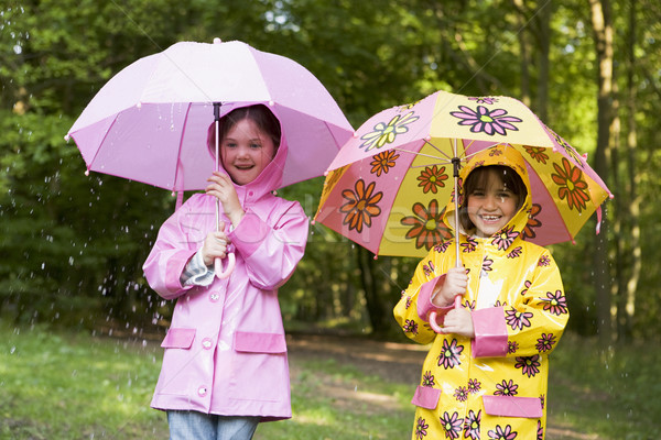 Two sisters outdoors in rain with umbrellas smiling Stock photo © monkey_business