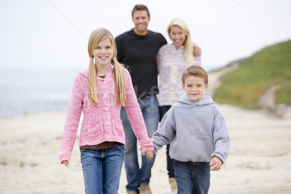 Family walking at beach holding hands smiling Stock photo © monkey_business