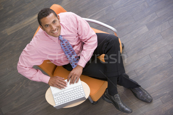Businessman sitting indoors with laptop smiling Stock photo © monkey_business