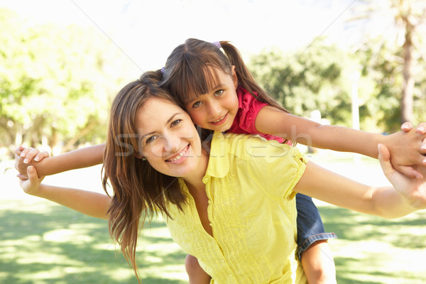 Mother Giving Daughter Ride On Back In Park Stock photo © monkey_business