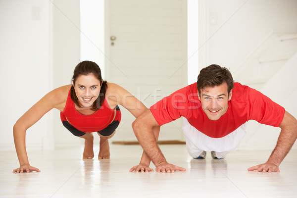 Couple doing push-ups in home gym Stock photo © monkey_business