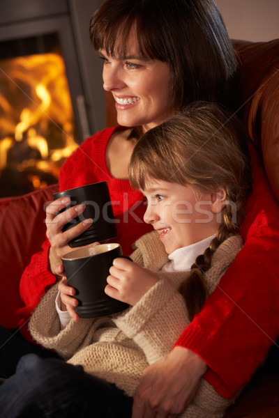 Mother And Daughter Relaxing With Hot Drink Watching TV By Cosy  Stock photo © monkey_business