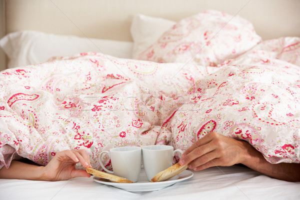 Couple's Hands Reaching From Under Duvet For Breakfast Stock photo © monkey_business