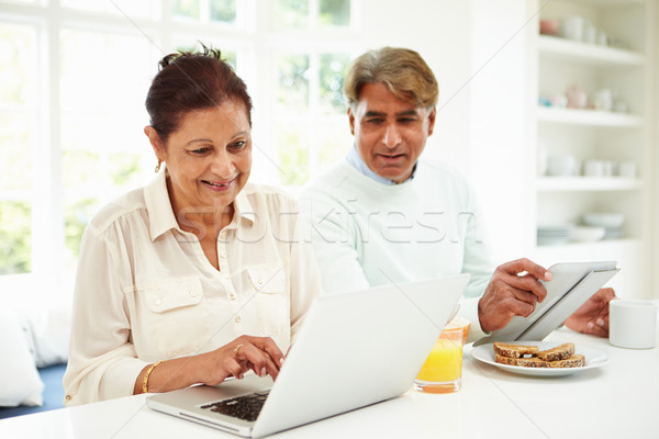 Stock photo: Senior Indian Couple Using Laptop And Digital Tablet At Home