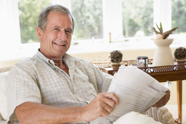 Stock photo: Man in living room reading newspaper smiling