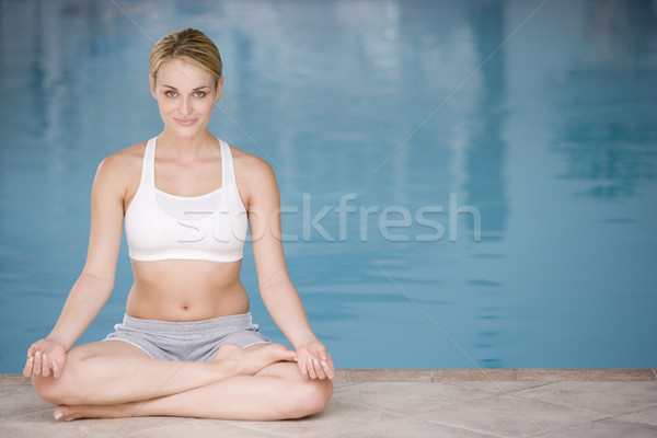 Woman sitting poolside doing yoga smiling Stock photo © monkey_business