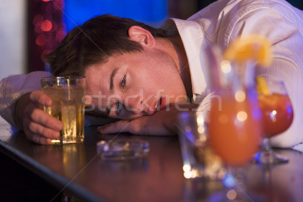 Drunk young man resting head on bar counter Stock photo © monkey_business