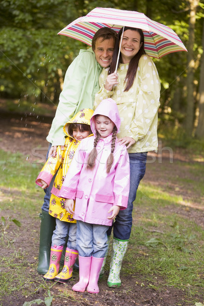 Family outdoors in rain with umbrella smiling Stock photo © monkey_business
