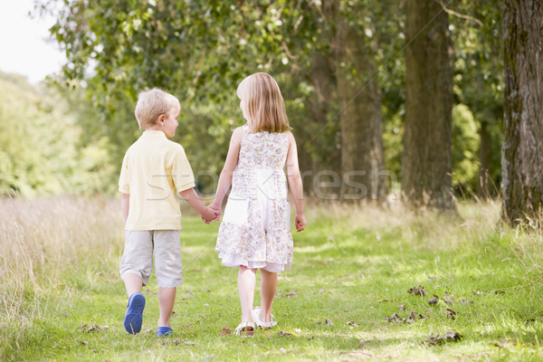 Two young children walking on path holding hands Stock photo © monkey_business