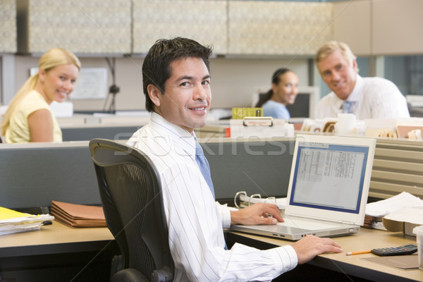 Businessman in cubicle with laptop smiling Stock photo © monkey_business