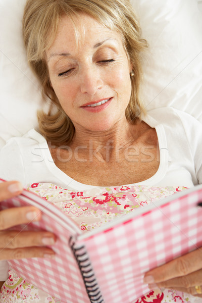 Senior Woman Relaxing In Bed Reading Diary Stock photo © monkey_business