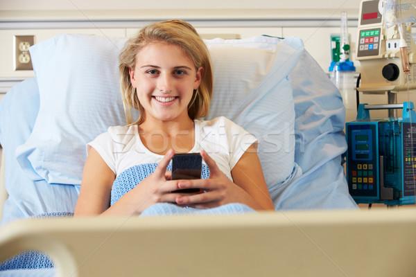 Adolescente feminino paciente telefone móvel cama de hospital feliz Foto stock © monkey_business