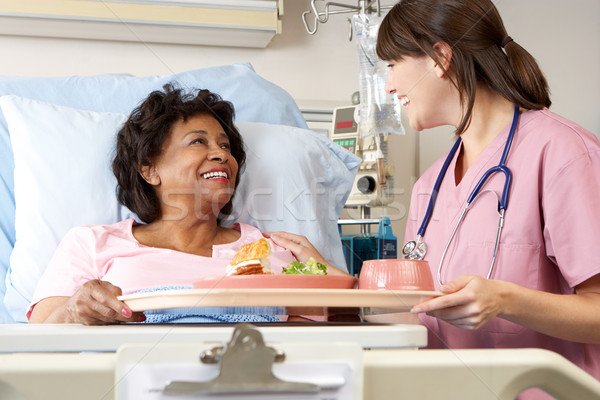 Nurse Serving Senior Female Patient Meal In Hospital Bed Stock photo © monkey_business