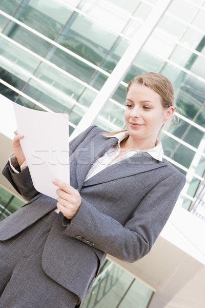 Businesswoman standing outdoors reading paperwork Stock photo © monkey_business