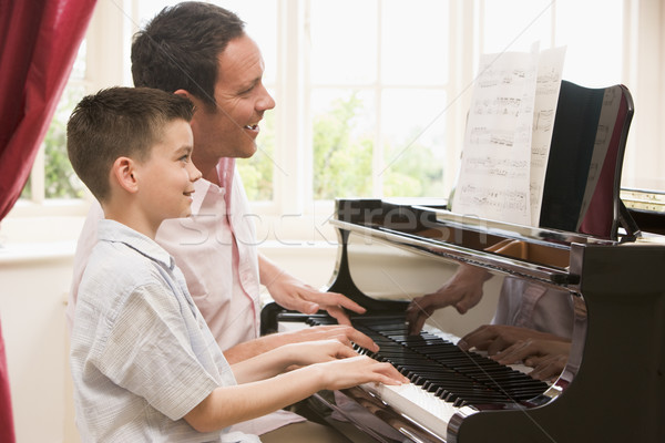 Stock photo: Man and young boy playing piano and smiling