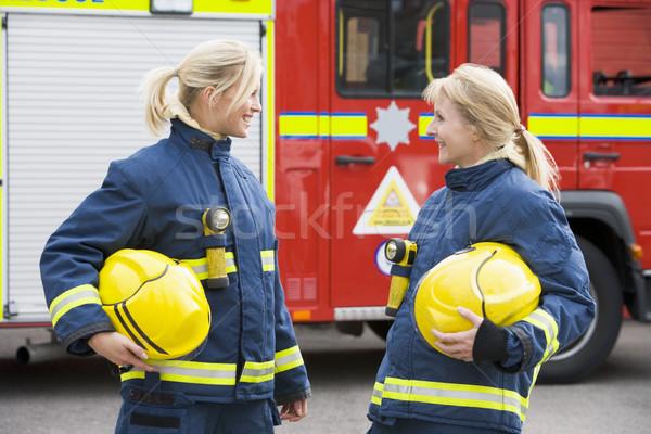 Stockfoto: Twee · vrouwelijke · brandweerlieden · brandspuit · glimlachend · helm