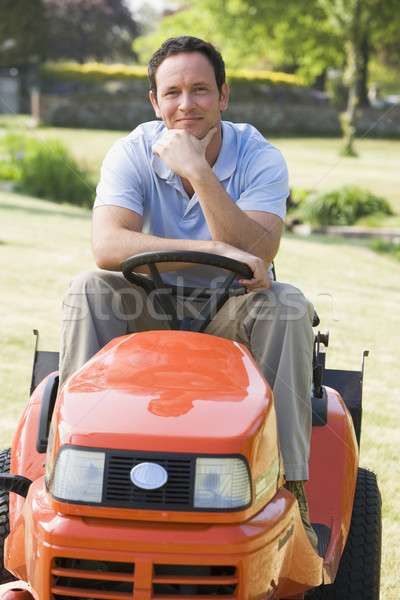 Man outdoors on lawnmower smiling Stock photo © monkey_business