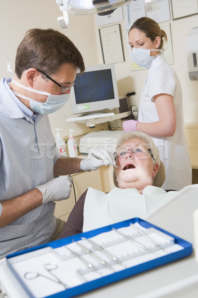 Dentist and assistant in exam room with woman in chair Stock photo © monkey_business
