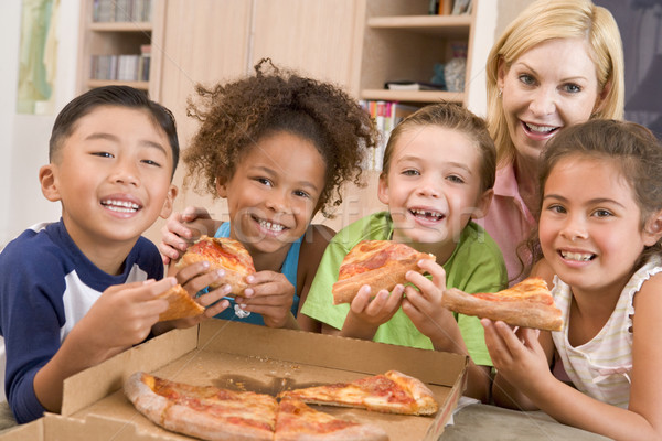 Four young children indoors with woman eating pizza smiling Stock photo © monkey_business