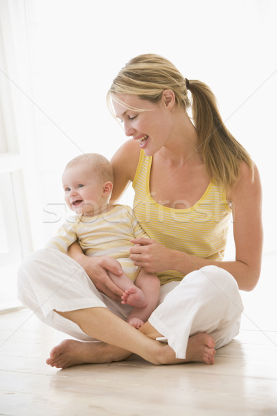 Mother and baby sitting indoors smiling Stock photo © monkey_business