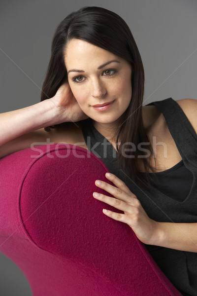 Studio Portrait Of Woman Relaxing On Pink Chaise Longue Stock photo © monkey_business