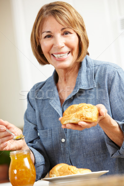 Mid age woman eating croissants Stock photo © monkey_business