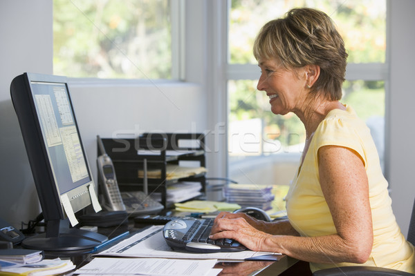 Woman in home office using computer smiling Stock photo © monkey_business