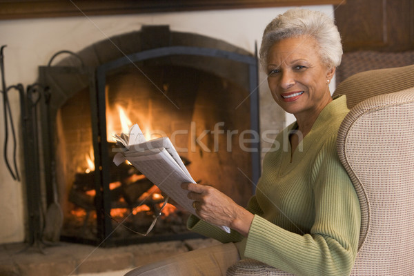 Woman sitting in living room by fireplace with newspaper smiling Stock photo © monkey_business