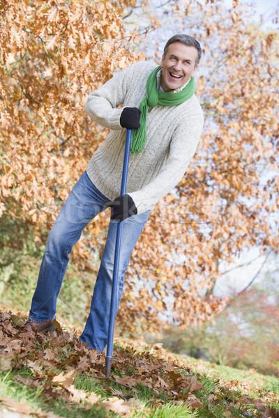 Senior man tidying leaves in garden Stock photo © monkey_business