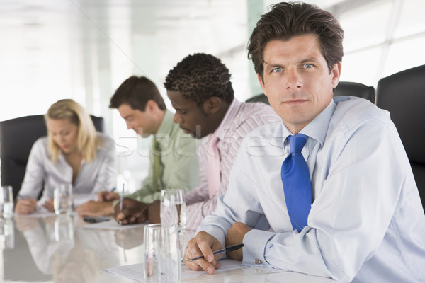 Four businesspeople in a boardroom writing Stock photo © monkey_business