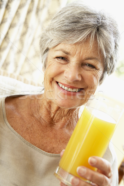 Senior vrouw glimlachen camera drinken sinaasappelsap vrouw Stockfoto © monkey_business