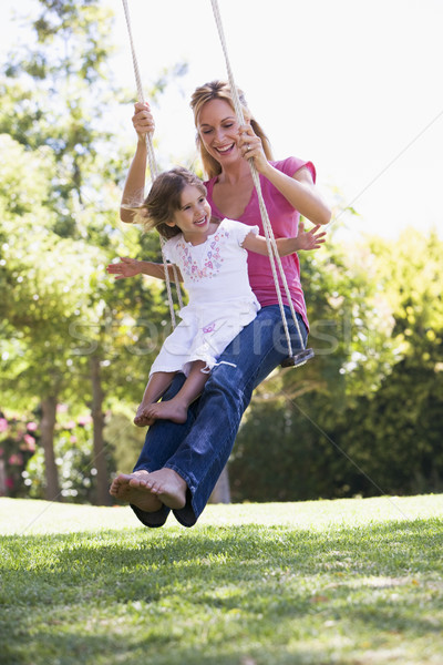Woman and young girl outdoors on tree swing smiling Stock photo © monkey_business