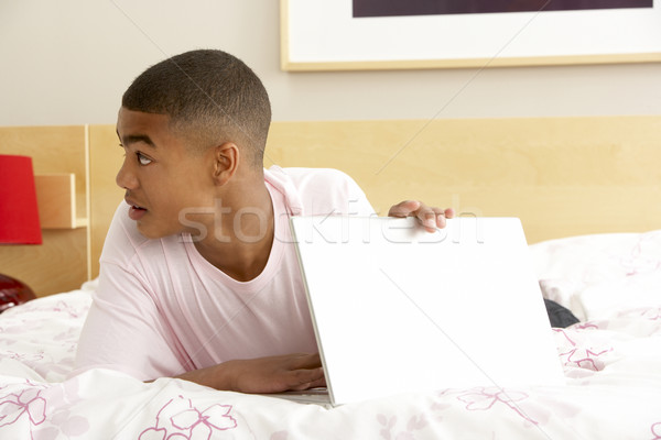 Guilty Teenage Boy Using Laptop In Bedroom Stock photo © monkey_business