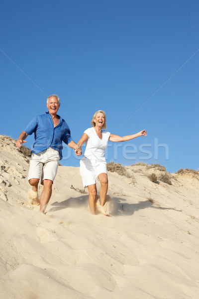 Senior Couple Enjoying Beach Holiday Running Down Dune Stock photo © monkey_business