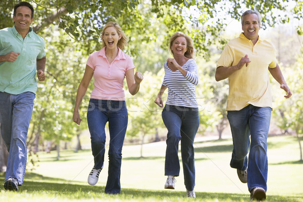 Two couples running outdoors smiling Stock photo © monkey_business