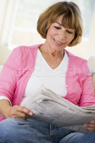 Woman in living room reading newspaper smiling Stock photo © monkey_business